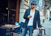 Young man on street. Trendy young man walking on street with bicycle using smartphone poster