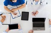medicine, healthcare and cardiology concept - group of doctors with cardiogram, clipboard, tablet pc poster