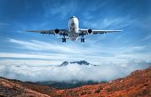Airplane Is Flying Over Low Clouds And Mountains poster