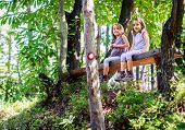 Twin Girls Resting And Sitting On Bench In Woods. poster