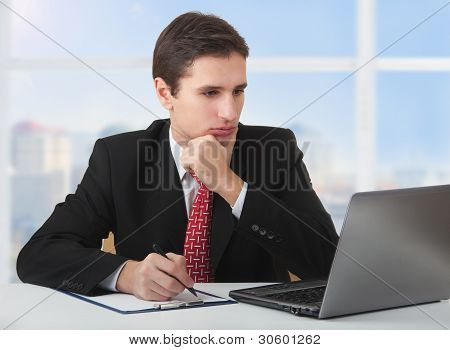 Young Successful Business Man Working Behind The Notebook, Sitting At A Desk