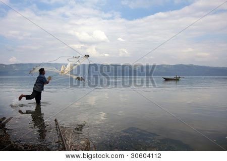 SUMATERA - FEBRUARY 10: A fisherman casts his net into Lake Singkarak, a tectonic lake in Sumatera, Indonesia on Feb 10, 2012. It is the biggest lake in Sumatera measuring 20km long and 8km wide.