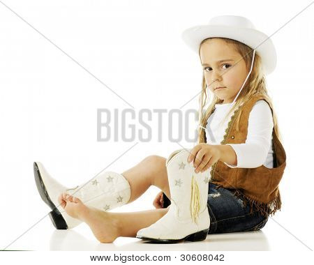 An adorable little cowgirl putting on her boots.  On a white background.