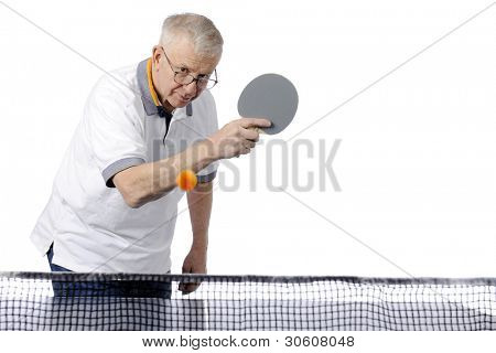 A senior man experienced at ping pong ready to spin the approaching ball back across the net with a backhanded stroke.  Motion blur on ball.  Horizontal orientation with white space for your text.