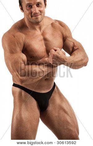 Guapo culturista flexionando sus músculos en estudio