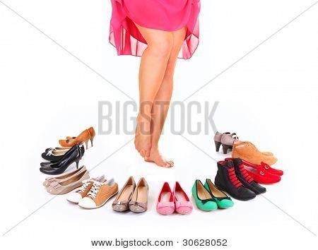 Ein Bild eine hübsche junge Frau sitzt im Kreis der Schuhe over white background