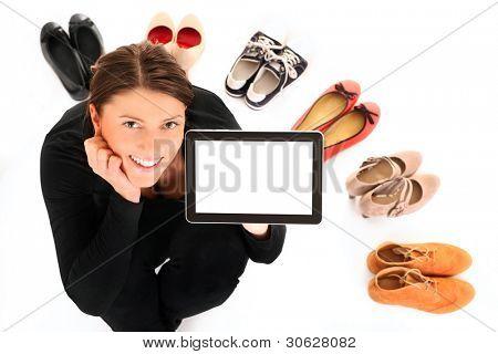 ein Bild, ein hübsche junge Frau sitzend im Kreis der Schuhe mit Tablet over white background