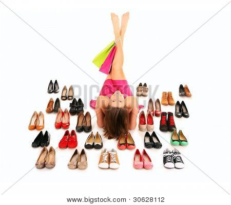 Ein Bild von eine hübsche junge Frau, liegend unter Schuhe over white background