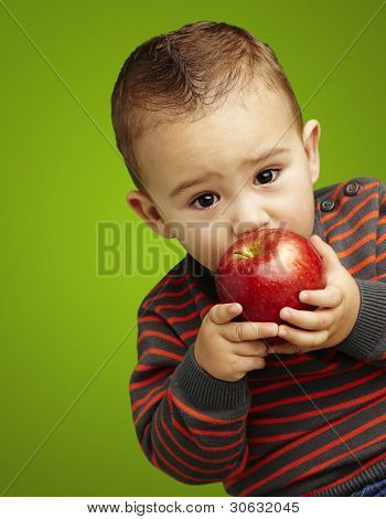 portrait of a handsome kid sucking a red apple over green background