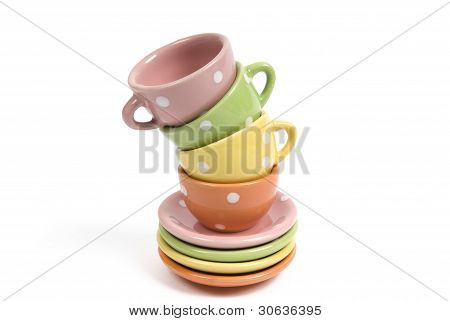 Four colourful teacups balancing on stacked saucers