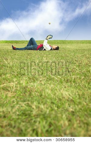 young man lying on the grass field and playing baseball