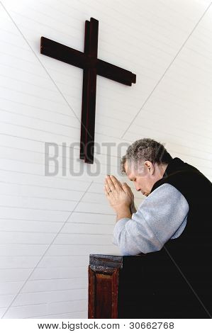 Man Praying at Wooden Cross