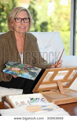 senior woman painting at home
