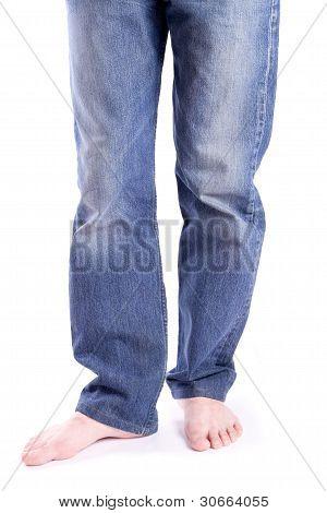 Men's feet barefoot in jeans