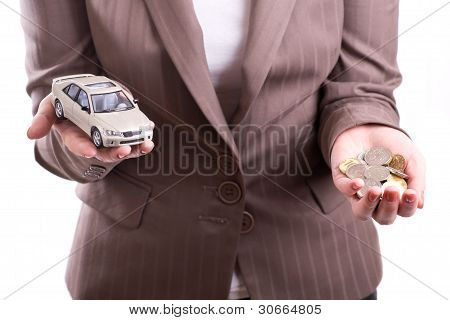 Hand holding the model of car and coins
