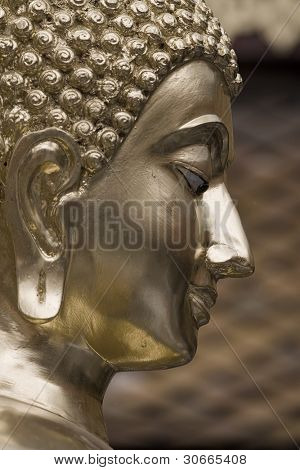 head of a golden buddha in a warm atmosphere