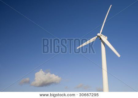 simple wind turbine isolated over a blue sky with one cloud. Alternative energy source