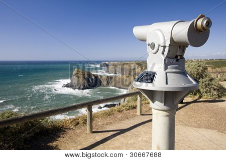Coin operated telescope in a coastline viewpoint overlooking the ocean (Pay per view concept)