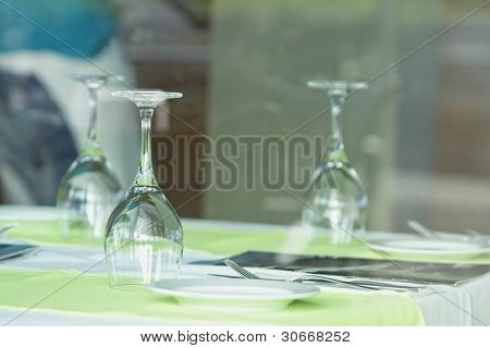 Table setting at a European restaurant. Glasses of wine set on dining table (Selective focus on front glass)