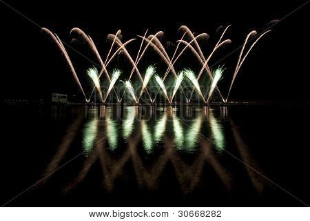 Long exposure photo of multiple fireworks over a lake, against a black sky.