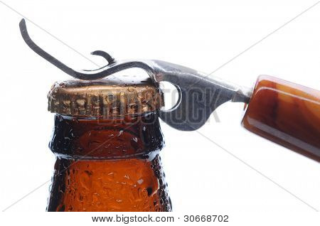 Macro shot of a brown beer bottle with an opener ready to pry up the bottle cap. Horizontal format over white.