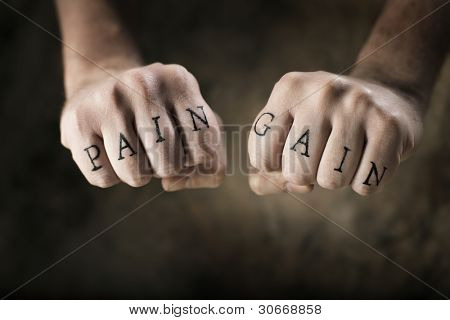 "Man with fake tattoos ""Pain"" and ""Gain"" on his hands, referring to the exercise motto ""No Pain, No Gain""."