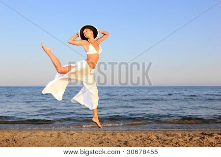 young woman in bikini jumping on the beach