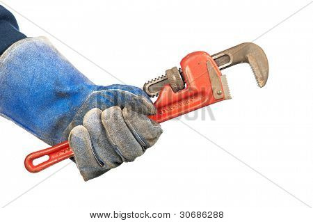 A man holding an old, rusty plumbers pipe wrench while wearing worn out workshop gloves.