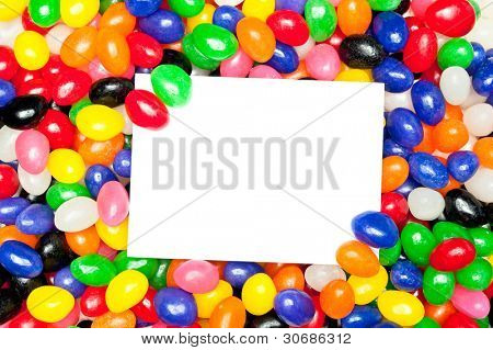 A blank message card in a pile of colorful jellybeans.  Designers can use card to place copy.