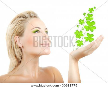 Beautiful woman holding fresh clover plant  in hand, sensual female portrait isolated on white background, cute girl with bright green makeup, st.Patrick's day holiday