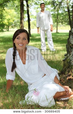 Woman in white sitting in a park with her husband in the background