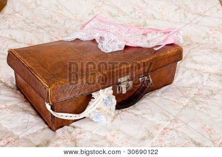 Vintage garter with blue bow in a suitcase waiting for the bride