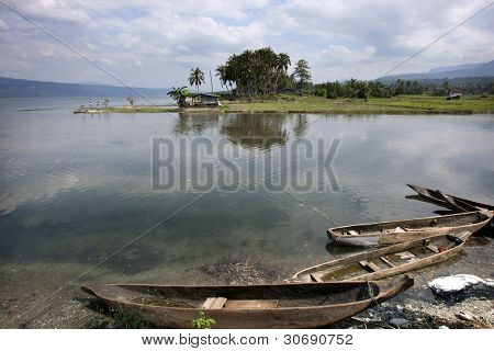 Fishing boats and calm waters reflection the skies at lake Singkarak, the largest tectonic lake in Sumatera, Indonesia.