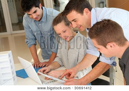 Educator with students in architecture working on electronic tablet