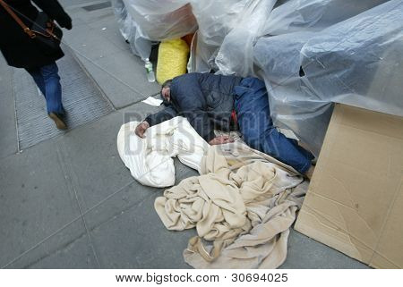 NEW YORK - FEBRUARY 12: A pedestrian walks past a homeless man sleeping on 33rd Street near 8th Avenue on February 12, 2005 in New York City.