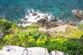 Looking Over A Cliff Edge With Blue Sea Below And Cliff Edge And The Sea. Stones Worn Smooth Along T poster