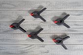 Several Black And Red Spring Clamps On The Wooden Boards poster