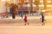 Nordic Walking,a Couple Actively Engaged In Nordic Walking On The Beach. poster