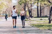 Young Sportsman And Sportswoman Smiling While Jogging Along Park Alley poster