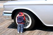 image of partially clothed  - Childlike doll leaning against the wheel of an antique car - JPG