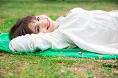 Happy Pretty Young Woman Lying And Relaxing On Lawn. Lady Looking At Camera And Resting On Blanket O poster