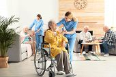 Nurse Giving Glass Of Water To Elderly Woman In Wheelchair At Retirement Home. Assisting Senior Peop poster