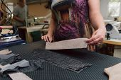A Woman Strokes The Fabric For Further Sewing. Tailor Ironing Clothes With Industrial Iron. poster