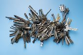 Bunch Of Keys For Locksmith. Set Of Keys On Blue Background. Collection Of Antique And Modern Keys. poster