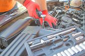 Auto Mechanic Working In Garage During The Maintenance Of Engine. Mechanician Holding Wrench Tool Du poster