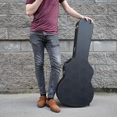 Man Put His Foot On A Hard Guitar Case. Hard Case For Electric Guitar. Man Dressed In Jeans Holding  poster