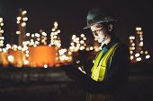 Asian Man Engineer Using Digital Tablet Working Late Night Shift At Petroleum Oil Refinery In Indust poster
