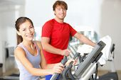 Fitness center people smiling happy working out on moonwalker fitness machines in fitness center. As