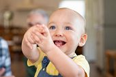 Excited toddler looking up with extended hands. Cute little boy showing hands and playing at home. C poster
