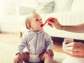 family, food, child, eating and parenthood concept - mother with puree and spoon feeding little baby poster